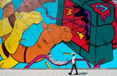 TOPSHOT - A worker wearing a hard hat walks past a mural in Dubai on June 3, 2020. - Shopping malls in Dubai will fully reopen for business on June 3, in the latest easing of COVID-19 coronavirus restrictions, the emirate's media office announced. The step makes the glitzy city-state the first in the Middle East to drop nearly all restrictions to combat the spread of the novel coronavirus that hit retailers and leisure activities. (Photo by Karim SAHIB / AFP) (Photo by KARIM SAHIB/AFP via Getty Images)